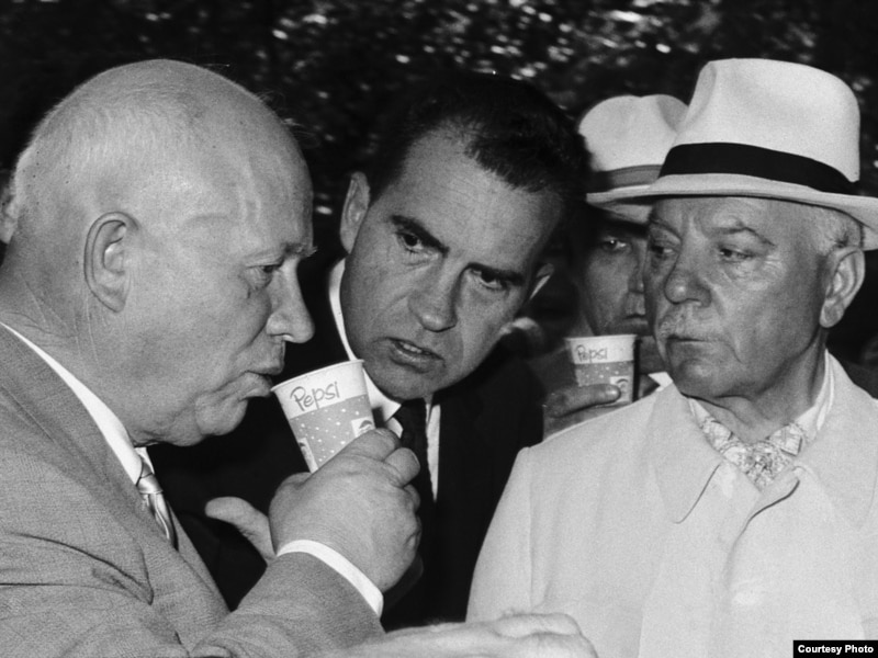 Никита Хрущев (слева) пьет пепси-колу, за ним наблюдает Ричард Никсон (в центре). Американская выставка в Москве, июль 1959 года.