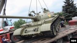 Узброеныя прарасейскія баевікі загружаюць стары танк расейскай вытворчасьці зь мясцовага музэя Вялікай Айчыннай вайны на трэйлер, транспартаваць у раён Данбасу. Украіна, 7 ліпеня 2014 году