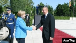 German Chancellor Angela Merkel (left) is greeted by Azerbaijani President Ilham Aliyev in Baku on August 25.
