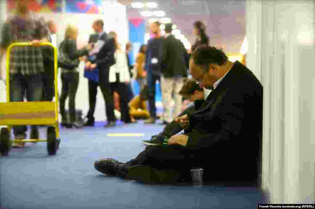 A journalist takes a seat on the floor near the short film section of the festival.
