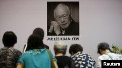 Ли Куан Юнун портретинин алдында турган адамдар. Сингапур.