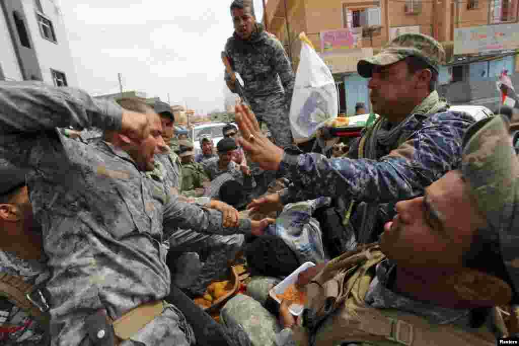 """Один из иракских военнослужащих бьет взятого в плен в Тикрите боевика, воюющего на стороне террористической организации """"Исламское государство"""""""