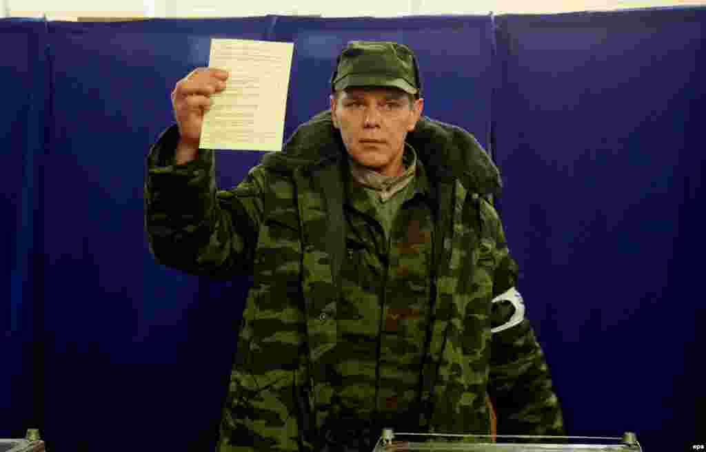 "A member of the pro-Russian ""self-defense"" forces that emerged in Crimea alongside the Russian occupation shows his ballot at a polling station."