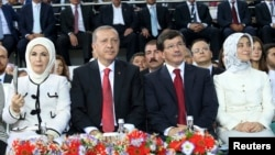 Turkish Prime Minister Tayyip Erdogan (2nd left) and Foreign Minister Ahmet Davutoglu (2nd right) are accompanied by their wives, Emine Erdogan (left) and Sare Davutoglu (right), as they attend the Extraordinary Congress of the ruling AKP on August 27.