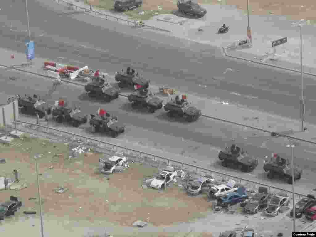 """Бахрейн. Ордо шаар Манаманын көчөлөрүндөгү аскер унаалары. Бермет аянтынан бир көрүнүш. 6-сүрөт. 17.3.2011. Nick. - 2011-жылдын 17-мартында (бейшембиде) Бахрейн падышалыгынын коопсуздук күчтөрү Манама шаарынын көчөлөрүн жана аянттарын көзөмөлдөөсүн улантты. Алар шийи араптар басымдуулук кылган демонстранттарды 16-мартта күч менен таркаткан. Ишкер Ник """"Азаттыкка"""" жиберген сүрөттөрдөн. Манама ш., Бахрейн. 17.03.2011. № 6-сүрөт."""