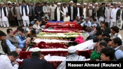 People gather to attend a funeral for the victims of the market blast at a graveyard in Quetta on April 12.