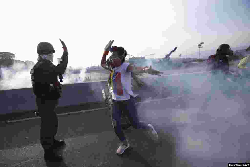 An opponent of Venezuelan President Nicolas Maduro high fives a rebel soldier on a highway overpass outside La Carlota air base amid tear gas fired by loyalist troops inside the base in Caracas on April 30. (AP/Boris Vergara)