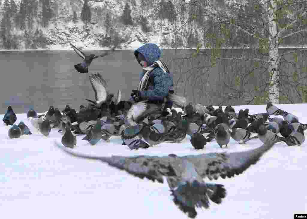 A boy feeds pigeons on a snow-covered embankment of the Yenisei River in the Siberian town of Divnogorsk, Russia. (Reuters/Ilya Naumushin)