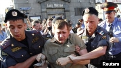 "Police detain an opposition activist taking part in the ""Day of Wrath"" protest rally in central Moscow on June 28."