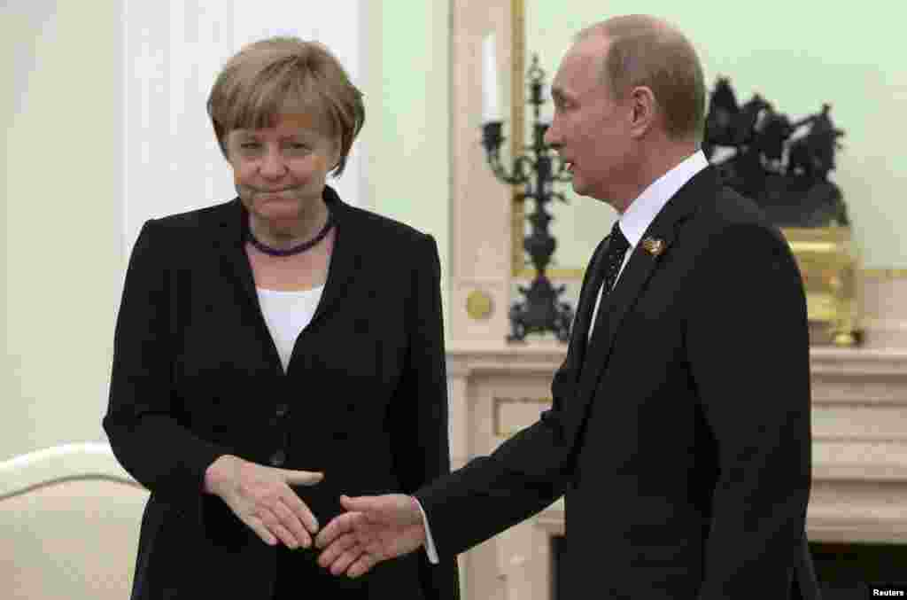 Russian President Vladimir Putin and German Chancellor Angela Merkel exchange an awkward handshake during a meeting at the Kremlin to discuss the Ukraine crisis. Merkel reiterated her calls to Putin to use his influence with pro-Russian separatists to end the conflict. (Reuters/Sergei Karpukhin)