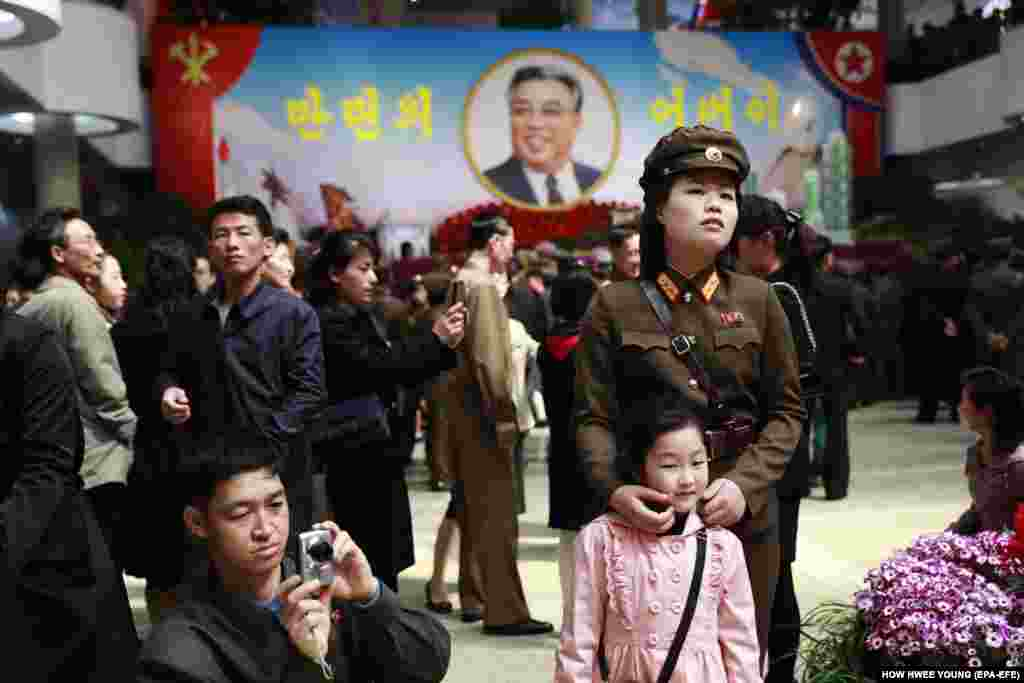 A soldier and her child attend a flower exhibition, part of celebrations marking the 105th anniversary of the birth of the late supreme leader Kim Il-sung in Pyongyang, North Korea, April 16, 2017. (EPA-EFE/How Hwee Young)