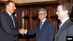 Russian President Dmitry Medvedev (right) looks on as his counterparts Serzh Sarkisian (center) and Ilham Aliyev shake hands at talks over Nagorno-Karabakh in 2008. Can Russia bring an end to such conflicts in the former Soviet space?