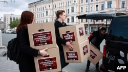 Moscow gay-rights activists carry boxes reportedly containing signed petitions calling for a probe into reported abuse in Chechnya in May 2017.