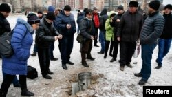 People look at the remains of a rocket that hit a residential street in the eastern town of Kramatorsk on February 10.