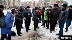 Stanovnici pored rakete koja je pala tokom granatiranja u Kramatorsku, gradu na istoku