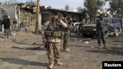 Security forces keep watch at the scene of a suicide bombing in Helmand Province
