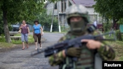 Women walk toward a Ukrainian government soldier searching for members of Right Sector in the village of Bobovyshche, near Mukacheve, on July 13.