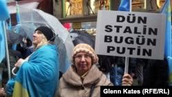 "Orsýetiň Krymdaky hereketlerine garşy protest aksiýasynyň gatnaşyjysy ""Düýn Stalin şu gün Putin"" diýen şygary tutup dur, Stambul, 8-nji mart, 2014."