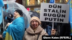 "A woman holds a sign reading, ""Yesterday Stalin, Today Putin"" at a protest in Istanbul against Russian actions in Crimea."