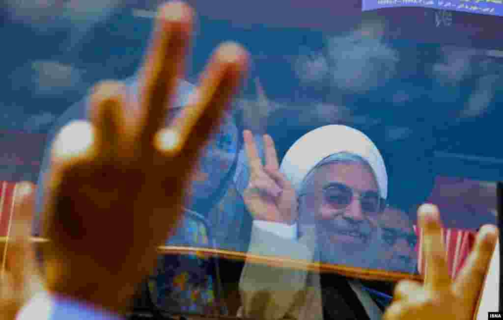 Rohani is seen behind protective glass as he greets supporters.
