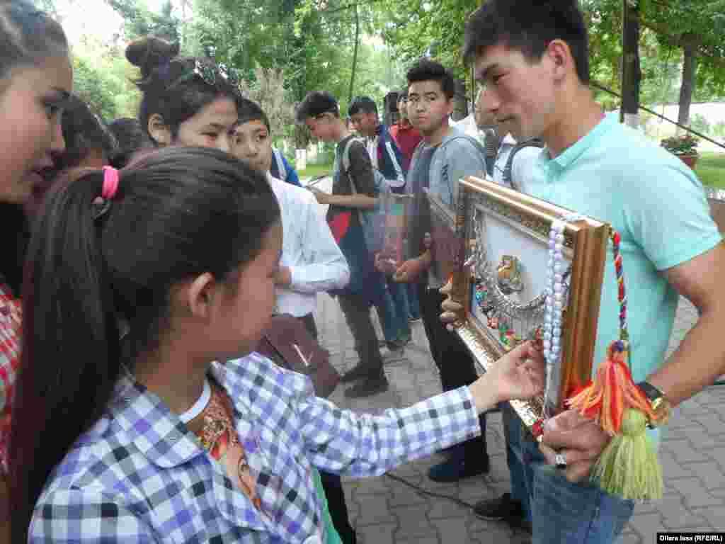 Дети рассматривают панно, созданное студентом Пердебеком Ергешем.
