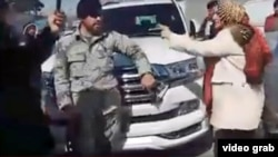Afghan parliamentary deputy Parwin Durrani confronts a police officer in Kabul on March 7, moments before she slapped him.