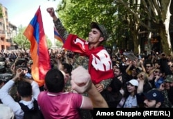 A soldier is carried through a crowd on the day Armenia's prime minister resigned amid massive street protests. Photo by Amos Chapple/RFE/RL