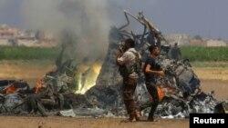 Люди около сбитого в Сирии 1 августа военного российского вертолета.
