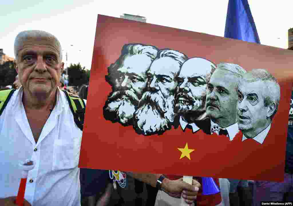 A protester holds a placard depicting Romania's leftist Social Democratic Party leaders in a lineup of Communist icons.