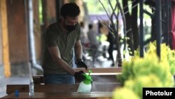 Armenia -- A waiter disinfects a table at a Yerevan cafe, May 4, 2020.