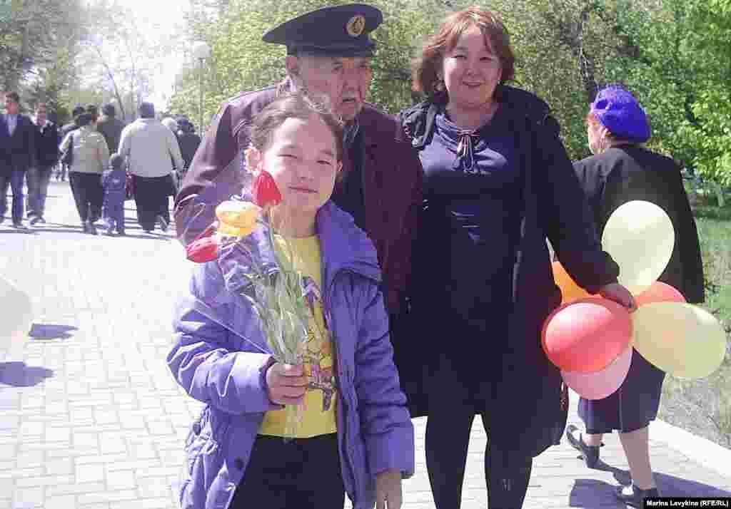 Внучка ведёт дедушку на парад Победы. Семей, 9 мая 2012 года.