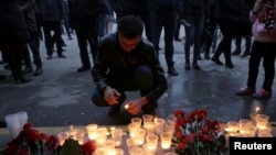 A man lights a candle during a memorial service for victims of a blast in the subway in St. Petersburg on April 3.