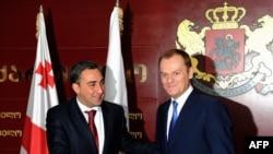 Georgian Prime Minister Nika Gilauri (left) welcomes Polish Prime Minister Donald Tusk to Tbilisi.