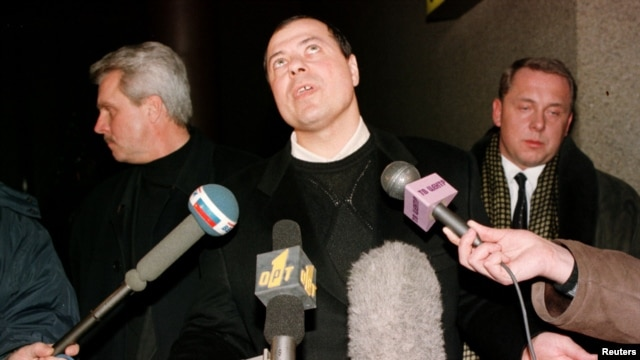 Sergei Mikhailov (center) speaks to the press at Moscow's Sheremetyevo airport on his return from Swizterland in this December 1998 file photo.