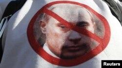 За осквернение портрета Владимира Путина чиханием оппозиционный активист получил 15 суток. В блогах размышляют, что будет с теми, кто носит подобную символику на своих футболках.