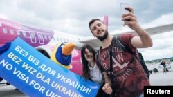 Пасажири з України фотографуються в аеропорту Гданська, Польща, 13 червня 2017 року