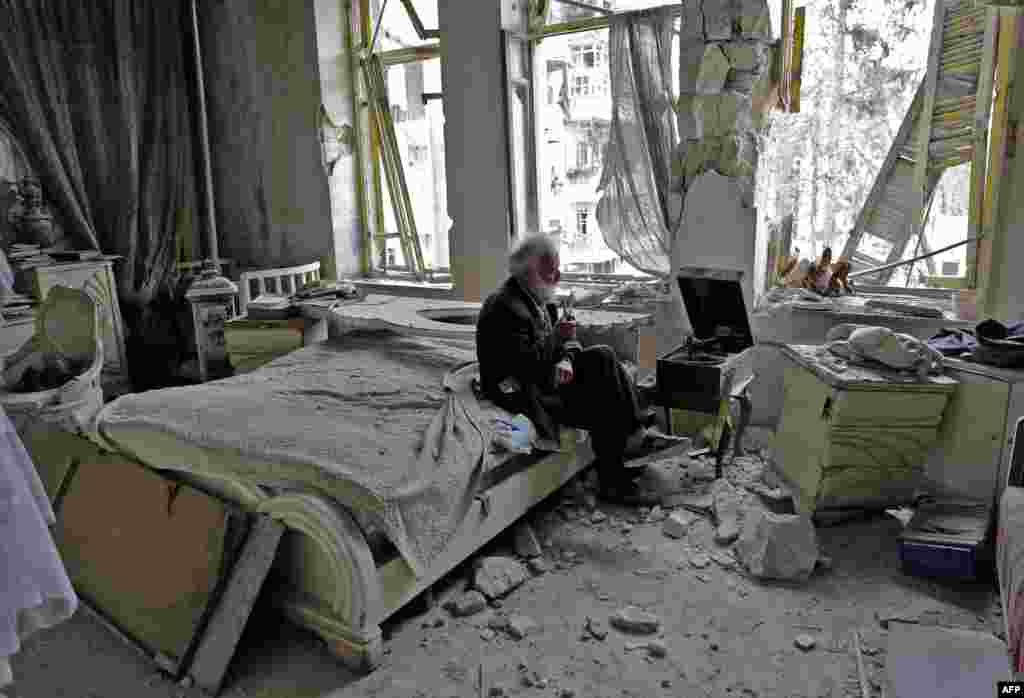 """70-летний мужчина курит трубку, слушая граммофон в своей разрушенной спальне с района Аль-Шаар в Алеппо. 9 марта. Старика зовут Мохаммед Анис. Он был владельцем косметической фабрики и коллекционировал старые автомобили. Большинство из его 24 машин были разрушены, несмотря на всего его старания: ему удалось убедить ополченцев не устанавливать зенитную пушку на """"Шевроле"""" 1958 года. Когда фотограф France-Press Джозеф Эйд познакомился с Анисом, он пригласил его в свой разрушенный бомбардировками дом. Войдя в спальню, Эйд обратил внимание на ручной граммофон и спросил Аниса, работает ли он. """"Конечно, – ответил тот. – Но сначала я должен раскурить трубку, я никогда не слушаю музыку без нее"""". Эйд считает, что сила снимка в том, что он «передает трагедию войны, не показывая насилие…Он просто рассказывает о воле к жизни». Эйду стало известно, что Анис новь запустил свой бизнес и восстанавливает дом."""