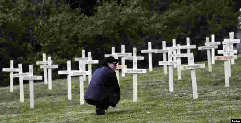 A man pays his respects in front of one of the wooden crosses.
