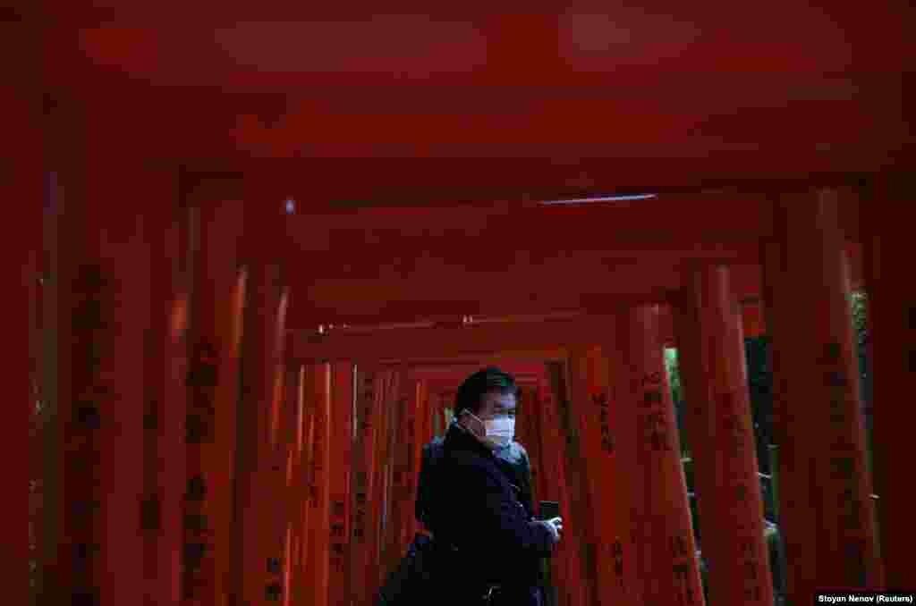 Маскі киген Токио тұрғыны Незу храмының тории қақпасынан өтіп бара жатыр. Жапониядағы вирус жұқтырғандар саны мың адамнан асып кетті. 5 наурыз 2020 жыл.