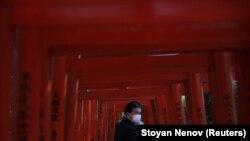 Беткап кийген эркек Токиодогу Незу ибадатканасынын жыгачтан жасалган дарбазасынын жанынан өтүп бара жатат. 5-март, 2020-жыл.&nbsp;<br /> <br /> &nbsp;
