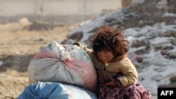 An Afghan girl sits next to aid for her family in Kabul.