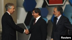 Turkish Foreign Minister Ahmet Davutoglu (center), accompanied by his Afghan counterpart Zalmay Rasul (right), shakes hands with U.S. Deputy Secretary of State William Burns before the Istanbul Conference on November 2.
