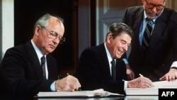 Liderul sovietic Mihail Gorbaciov (stânga) și președintele SUA Ronald Reagan semnând tratatul pentru eliminarea rachetelor de rază medie și scurtă cu încărcătură nucleară în cadrul summit-ului de la Washington, 8 decembrie 1987
