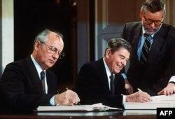 Mihail Gorbaciov (stânga) și Ronald Reagan (dreapta), la Washington, semnând, pe 8 decembrie 1987, tratatul de eliminare a rachetelor nucleare cu rază medie și scurtă de acțiune din arsenalul celor două țări