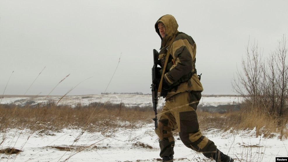 A separatist soldier walks in a field near the line of contact where a cease-fire is scheduled to take effect at midnight on December 24.