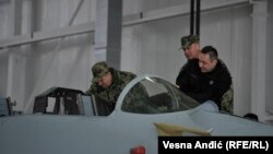 Serbian Defense Minister Aleksandar Vulin (in black) inspects a Russian MiG jet being upgraded at the Batajnica airfield.