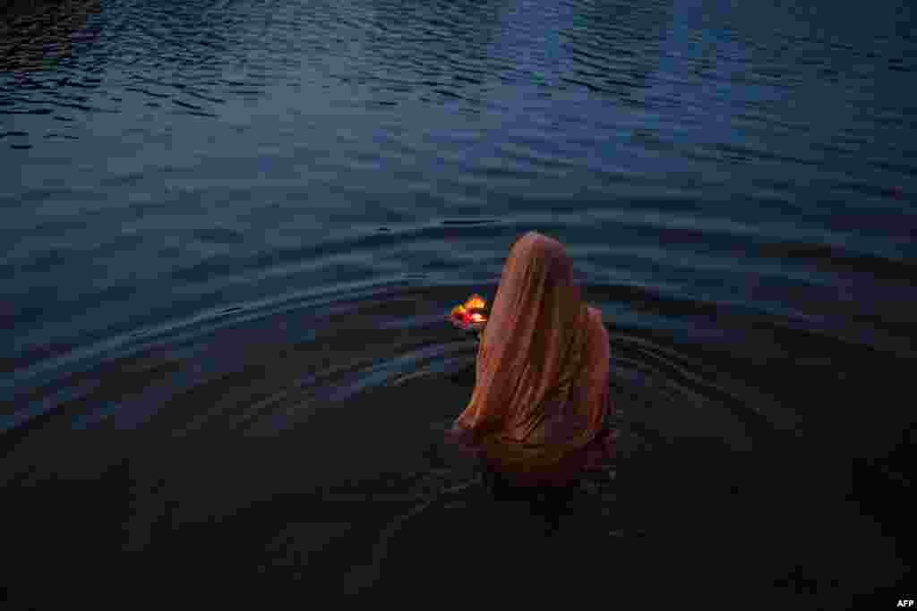 An Indian women offers early morning prayers early in the morning on the banks of the Betawa River in Orchha in the state of Madhya Pradesh. (AFP/Rebecca Conway)