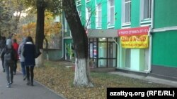 Прохожие рядом с офисным зданием, на котором висит объявление о сдаче в аренду. Алматы, 27 октября 2015 года.