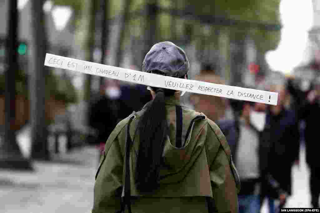 A woman wears a hat reading 'This is a one-meter hat. Please keep your distance' as she walks along the Champs Elysee avenue in Paris, France, 11 May 2020. France began a gradual easing of its lockdown measures and restrictions amid the COVID-19 pandemic.