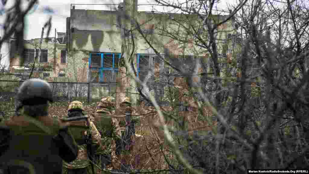 Ukrainian soldiers make their way past damaged buildings in Avdiyivka.